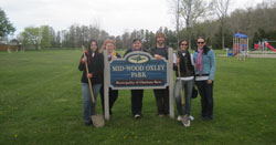 "Scribendi.com staff members stand with a sign in a Chatham park that reads: ""Mid-Wood Oxley Park."""