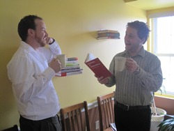 Two men are standing in a yellow room, each with a cup of coffee and one with a book. They are having an animanted conversation.