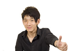 A male student who is wearing a black shirt and giving the thumbs up. He is happy because he just received a good college recommendation letter.