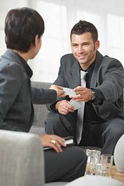 Two business people sitting on a lounge exchanging mini resumes and discussing their combination and targeted resumes.