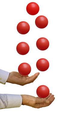 Two hands and several red balls being juggled.