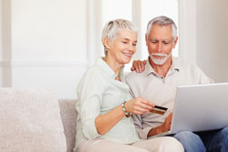 An elderly couple are sitting on a couch and placing an order on the Scribendi.com web site by using the Discover Card payment option.