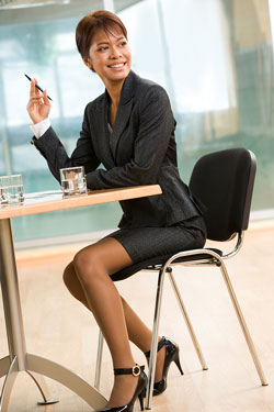 A business woman is sitting at a desk with a pen in her hand. She is writing an employee recommendation letter.