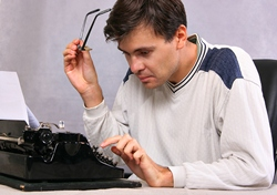 A man sitting infront of a typewriter, holding his glasses in one hand and typing with the other.