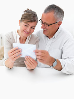 A middle-aged couple is sitting down and reading a formal letter.
