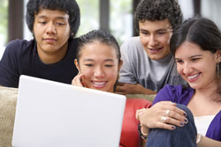 Four culturally diverse students sitting around a computer smiling. They are working on a homophone worksheet.