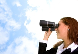 A brunette woman in a black shirt is holding binoculars and looking out at a blue sky with white fluffy clouds in it.
