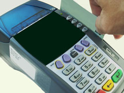An American express card is being run through a credit card terminal. American express is one of the payment options available at Scribendi.com.