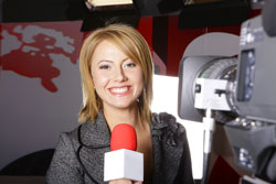 A female anchorwoman is delivering a press release example in front of the camera.