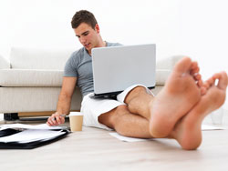A young man sits on his living room floor with a laptop and papers surrounding him; he is deciding if he should write a prologue for his book.