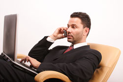 A publishing agent is sitting on a chair with his cell phone to his ear. He is reading a query letter sample.