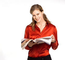 A young publisher is wearing a red shirt and holding a book.
