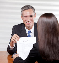 A man is handing a sample resume to a colleage for her to review.