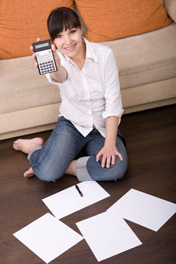 A young brunette woman is sitting on the floor of her house holding a calculator; there are pieces of paper that contain tax tips on the floor.