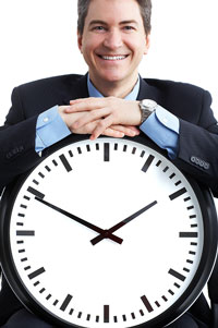 Business man standing with a large clock illustrating time management techniques.