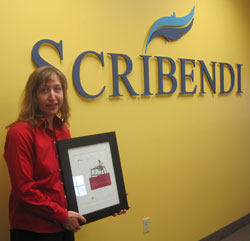 Scribendi.com President Chandra Clarke holds the VeriSign Certificate. She is standing in front of a Scribendi sign.