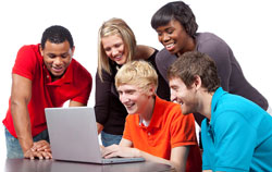 Five students dressed in casual attire are standing around a computer looking at the English Idioms website What Does That Mean?