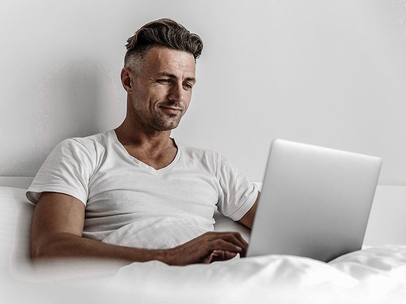 A man working on his laptop in bed.